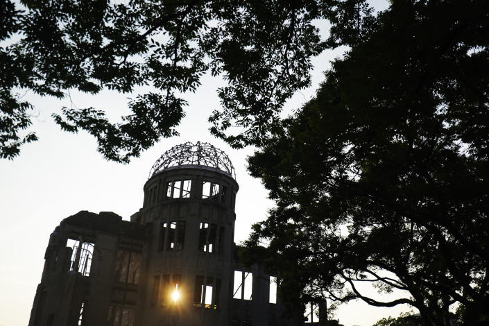 FILE - In this Aug. 2, 2020, file photo, the Atomic Bomb Dome is seen at dusk in Hiroshima, western Japan. Many residents of Hiroshima welcome attention to their city from abroad, which IOC President Thomas Bach will bring when he visits on Friday, July 16. But Bach will also bring political baggage — as will his vice president John Coates when he visits Nagasaki the same day — that is largely unwelcome in two cities viewed as sacred by many Japanese.(AP Photo/Eugene Hoshiko, File)