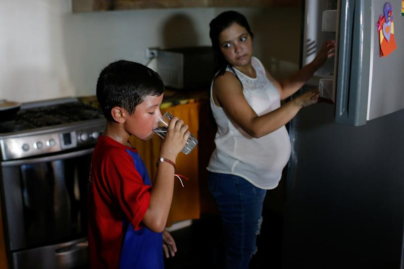 Baseball little league player Santiago Lopez, 10, drinks water after training at his house during an electricity cut in Maracaibo, Venezuela. (Photo: Manaure Quintero/Reuters)
