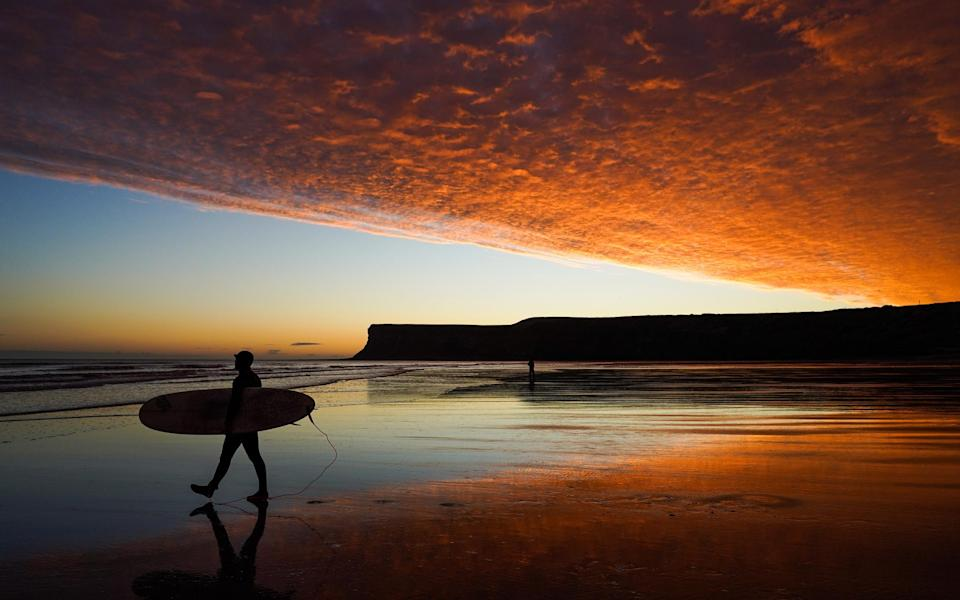 A surfer enjoys a spectacular sunset this afternoon - Getty