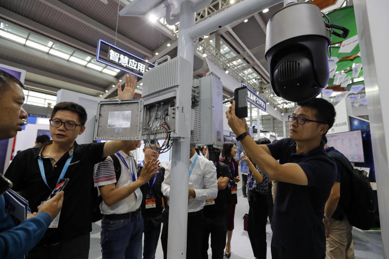 In this Tuesday, Oct. 29, 2019, photo, visitors look at the 5G mobile station and a surveillance camera by China's telecoms equipment giant Huawei on display at the China Public Security Expo in Shenzhen, China's Guangdong province. The U.S. Department of Commerce has proposed requiring case-by-case approvals of all purchases of telecommunications equipment in a move likely to hit major Chinese suppliers like Huawei. (AP Photo/Andy Wong)