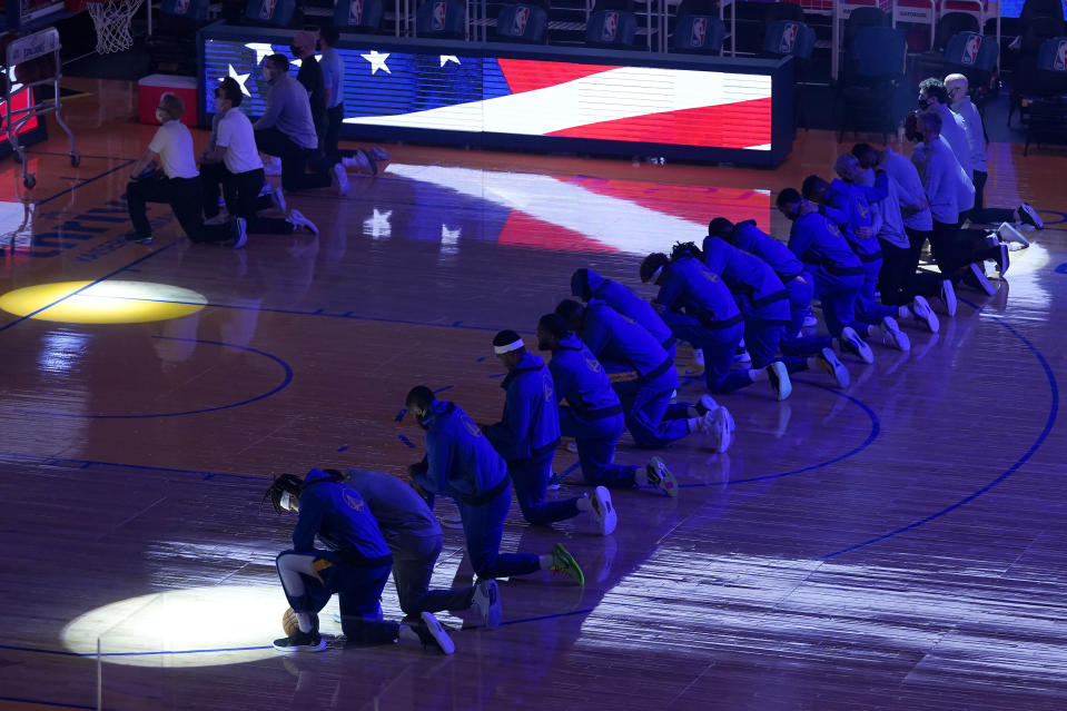 Golden State Warriors players and coaches kneel during the national anthem before an NBA basketball game against the Los Angeles Clippers in San Francisco, Wednesday, Jan. 6, 2021. (AP Photo/Jeff Chiu)