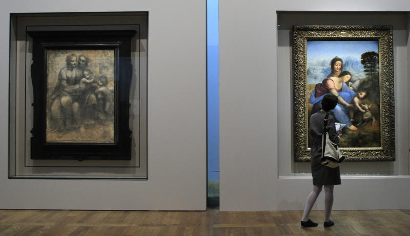 """A woman views the painting """"The Virgin and Child with Saint Anne"""", right, next to a preparation sketch, by Italian Renaissance master Leonardo da Vinci, at the Louvre Museum in Paris, Tuesday, March 27, 2012. A Da Vinci exhibition starts on Thursday with the unfinished artpiece """"The Virgin and Child with Saint Anne"""" as the star of a major exhibit exploring the work's genesis, and its place in art history. (AP Photo/Jacques Brinon)"""