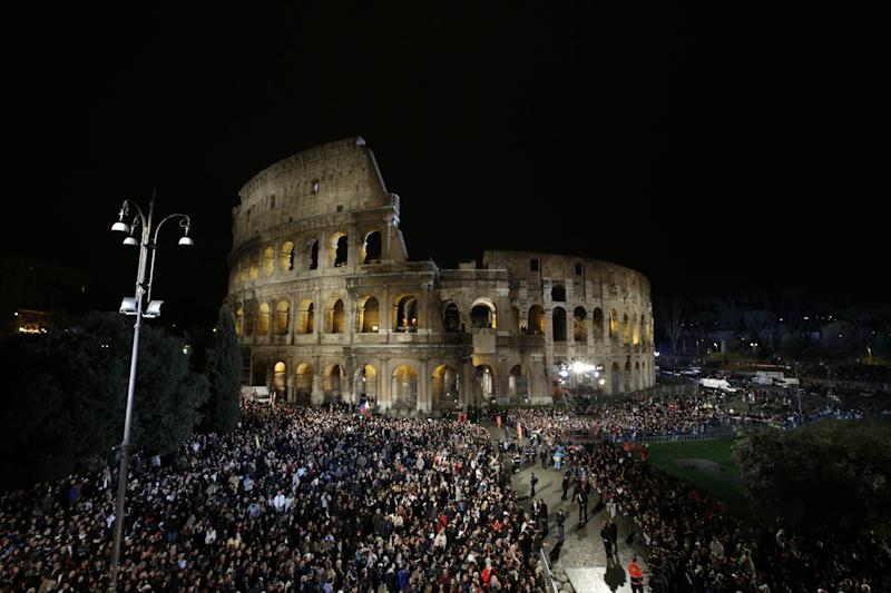 A crowd gathers beneath the ancient Colosseum prior to the start of the Via Crucis (Way of the Cross) torchlight procession which will be celebrated by Pope Francis, on Good Friday, in Rome, Friday, March 29, 2013. (AP Photo/Andrew Medichini)