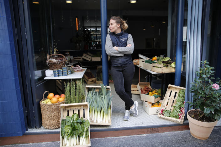FILE - In this Friday, March 27, 2020 file photo, chef Amandine Chaignot waits for customers as she turns her restaurant into a shop to sell vegetables during the lockdown of coronavirus, in Paris. European Union leaders are preparing for a new virtual summit, which will take place Thursday, April 23, 2020, to take stock of the damage the coronavirus has inflicted on the lives and livelihoods of the bloc's citizens and to thrash out a more robust plan to revive their ravaged economies. (AP Photo/Francois Mori, File)