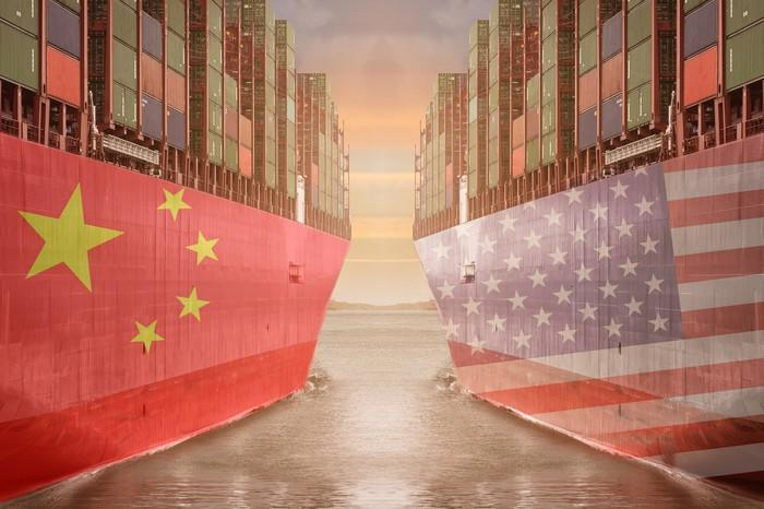 Two cargo ships next to each other, one with the Chinese flag and the other with the American flag.