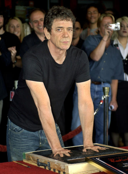 FILE - In a June 24, 2003 file photo, music icon Lou Reed has his hands imprinted as supporters cheer in the background as he is inducted into Hollywood's Rockwalk, in the Hollywood section of Los Angeles. Punk-poet, rock legend Lou Reed is dead of a liver-related ailment, his literary agen said Sunday, Oct. 27, 2013. He was 71.(AP Photo/Ric Francis, File)