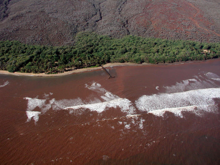 In this Nov. 23, 2003, photo provided by Ku'ulei Rodgers, muddy floodwater flows over a nearshore coral reef off the Hawaiian Island of Lanai after a heavy rainstorm. Flooding in March 2021, in Hawaii caused widespread and obvious damage. But extreme regional rain events that are predicted to become more common with global warming do not only wreak havoc on land, the runoff from these increasingly severe storms is also threatening Hawaii's coral reefs. (Ku'ulei Rodgers/University of Hawaii via AP)