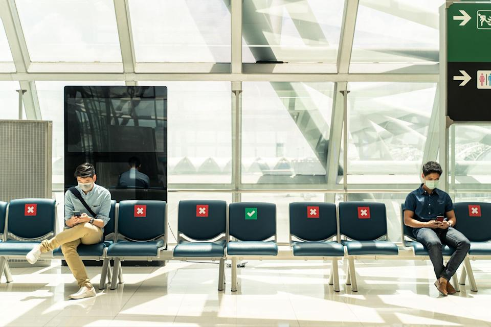 People social distancing at an airport.