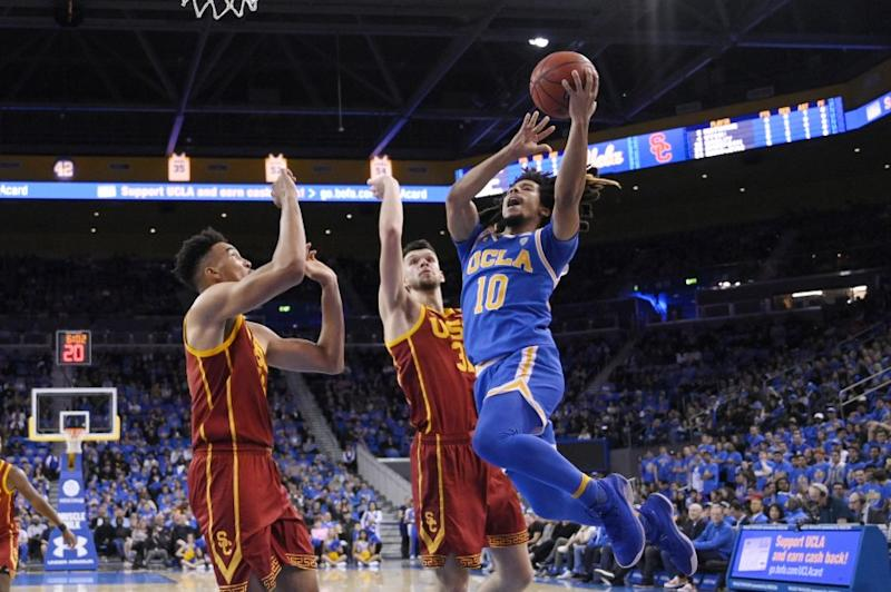 UCLA guard Tyger Campbell, right, shoots as Southern California forward Isaiah Mobley, left, and forward Nick Rakocevic defend during the first half of an NCAA college basketball game Saturday, Jan. 11, 2020, in Los Angeles. (AP Photo/Mark J. Terrill)