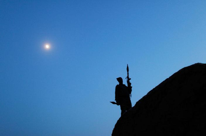 <p>An Afghanistan National Police member stands atop a building during a dusk raid June 22, 2010 in the Khushi Khona area of Afghanistan, in Herat Province near the Turkmenistan border. The 82nd Airborne along with NATO Italian troops have been working for nearly a year in this historic area of Afghanistan, dotted with ancient villages just north of the cosmopolitan city of Herat. (Photo by Chris Hondros/Getty Images) </p>
