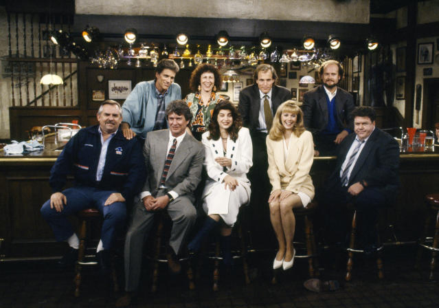 CHEERS — 'One for the Road' Episode 25 — Aired 5/20/93 — Pictured: (Back row l-r) Ted Danson as Sam Malone, Rhea Perlman as Carla Tortelli, Woody Harrelson as Woody Boyd, Kelsey Grammer as Dr. Frasier Crane (front row l-r) John Ratzenberger as Cliff Clavin, Tom Berenger as Don Santry, Kirsty Alley as Rebecca Howe, Shelley Long as Diane Chambers, George Wendt as Norm Peterson (Getty Images)