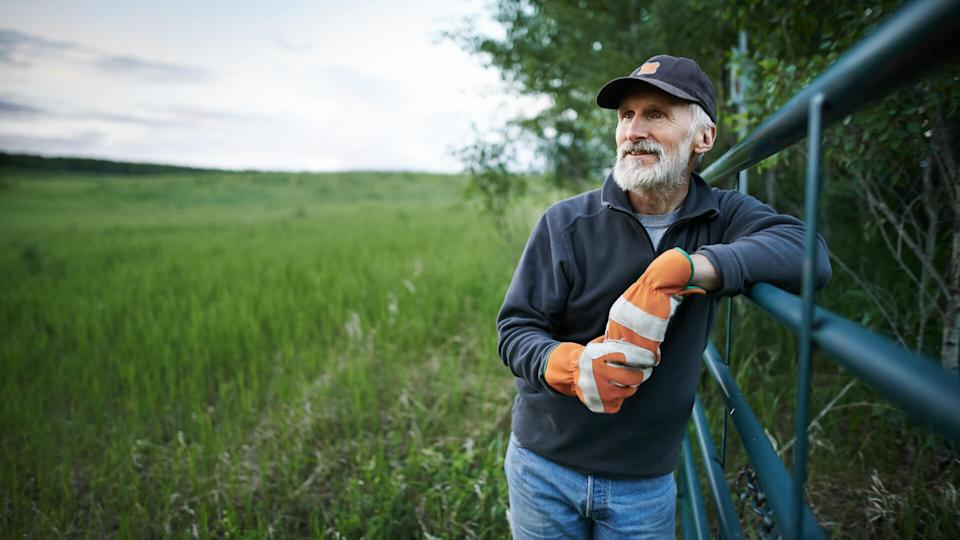 Shot of a mature man standing at the fence of a farm.