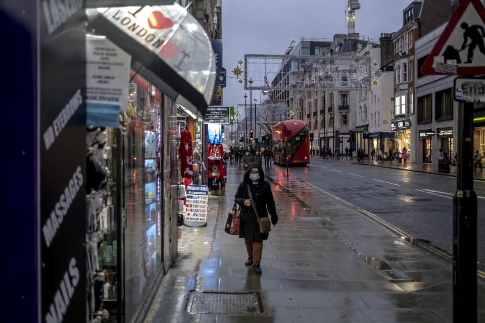 A woman walks on a rain-soaked Oxford Street on the first day of Tier 3 restrictions in London, on Dec. 16, 2020. (Andrew Testa/The New York Times)
