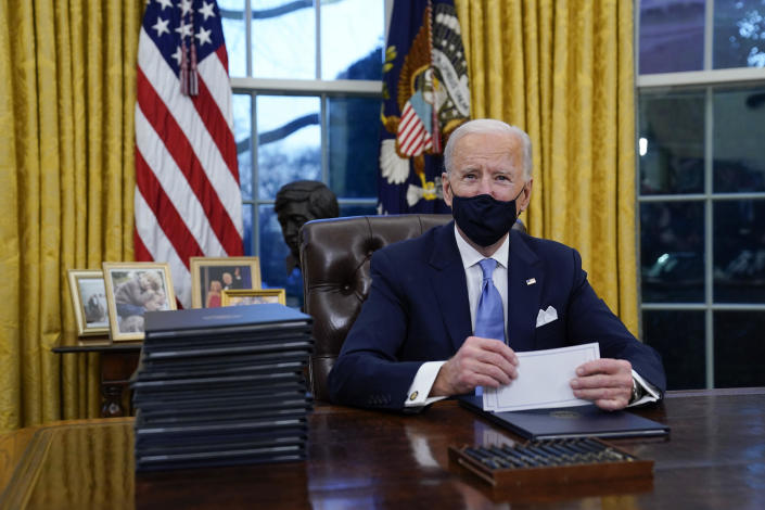President Joe Biden pauses as he signs his first executive orders in the Oval Office of the White House on Wednesday, January 20, 2021, in Washington, D.C. / Credit: Evan Vucci / AP