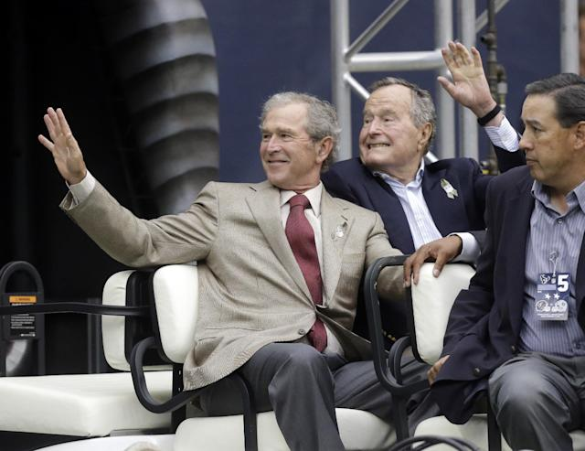 Former Presidents George H.W. Bush and George W. Bush wave as they leave the field before an NFL football game between the Houston Texans and the Oakland Raiders Sunday, Nov. 17, 2013, in Houston. (AP Photo/Patric Schneider)