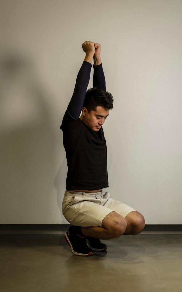 Former Hong Kong consulate worker Simon Cheng demonstrates the different poses state security officers forced him to stand in for hours each day as part of the torture he endured while being interrogated - OLIVIER MARCENY/OLIVIER MARCENY
