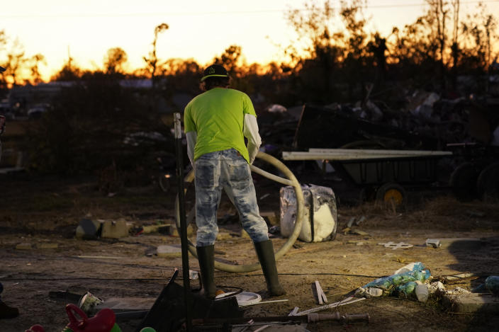Ricky Trahan sorts debris from his destroyed home, where he now lives in a tent with his wife, in the aftermath of Hurricane Laura and Hurricane Delta, in Lake Charles, La., Friday, Dec. 4, 2020. (AP Photo/Gerald Herbert)