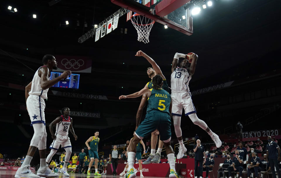 United States's Bam Adebayo (13) grabs a rebound over Australia's Patty Mills (5) and Nic Kay (15) during men's basketball semifinal game at the 2020 Summer Olympics, Thursday, Aug. 5, 2021, in Saitama, Japan. (AP Photo/Charlie Neibergall)
