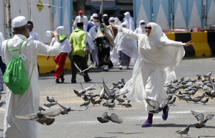 """FILE - In this Sunday, Aug. 4, 2019 file photo, a Moroccan pilgrim runs as pigeons fly outside the Grand Mosque in the Muslim holy city of Mecca, Saudi Arabia. The hajj is a pillar of Islam, required of all Muslims once in a lifetime. It is a physically demanding journey that Muslims believe offers a chance to wipe clean past sins and start anew before God. Pilgrims seek to deepen their faith on the hajj, with some women adopting the head covering known as the """"hijab."""" (AP Photo/Amr Nabil, File)"""