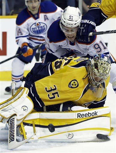 Nashville Predators goalie Pekka Rinne (35), of Finland, dives on the puck as Edmonton Oilers left wing Magnus Paajarvi (91), of Sweden, gets a glove in the face in the first period of an NHL hockey game on Monday, March 25, 2013, in Nashville, Tenn. (AP Photo/Mark Humphrey)