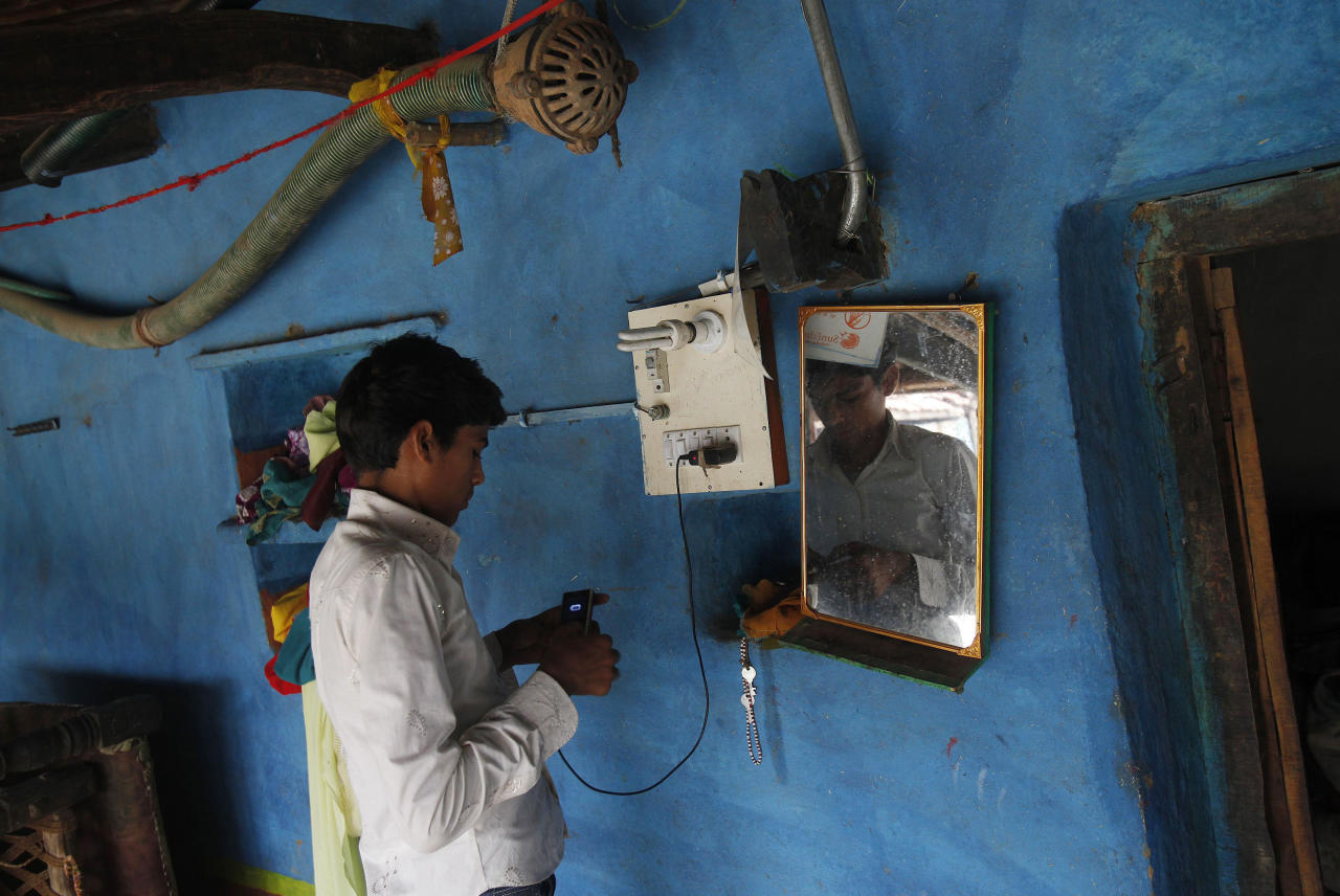 A boy charges his mobile phone from an electric board powered by solar energy inside his house at Meerwada village of Guna district in the central Indian state of Madhya Pradesh June 19, 2012. REUTERS/Adnan Abidi