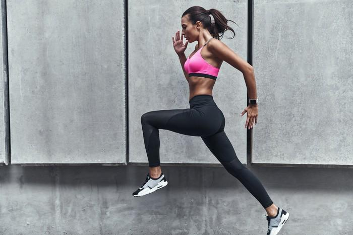 A young woman wearing athletic clothing while running.