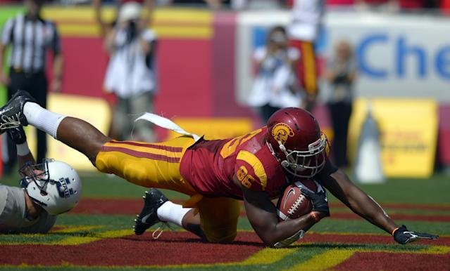 Southern California tight end Xavier Grimble, right, falls into the end zone for a touchdown as Utah State safety Brian Suite defends during the first half of an NCAA college football game on Saturday, Sept. 21, 2013, in Los Angeles. (AP Photo/Mark J. Terrill)