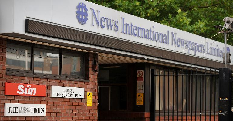 Signage for British national newspapers from News International, now News UK, outside the company's headquarters in east London, on July, 17, 2011