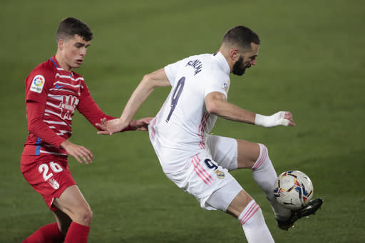 Real Madrid's Karim Benzema, right, and Granada's Alberto Soro vie for the ball during the Spanish La Liga soccer match between Real Madrid and Granada at the Alfredo Di Stefano stadium in Madrid, Spain, Wednesday, Dec. 23, 2020. (AP Photo/Bernat Armangue)