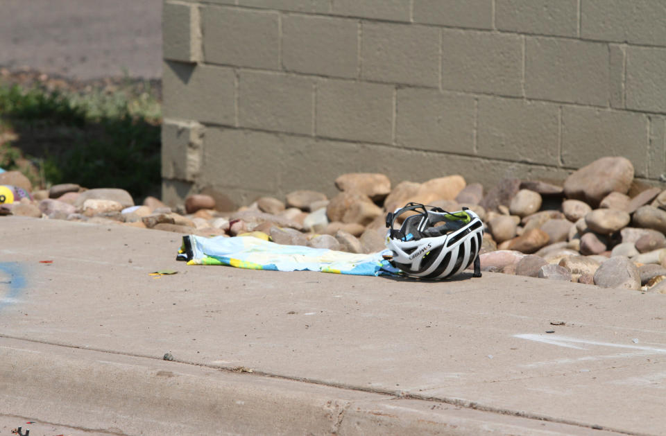 In this Saturday, June 19, 2021, photo courtesy of The White Mountain Independent is a cyclist's helmet at the scene of an accident in Show Low, Ariz. A driver in a pickup truck plowed into bicyclists competing in a community road race in Arizona on Saturday, critically injuring several riders before police chased down the driver and shot him outside a nearby hardware store, police said. (Jim Headley/The White Mountain Independent via AP)