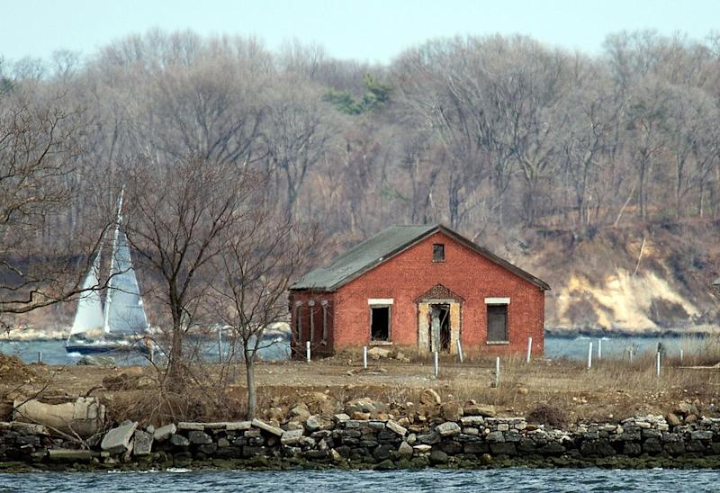 A sailboat passes behind an abandoned building on Hart Island on April 5, 2014 in New York. Each white plastic pipe near the building marks an infant mass gravesite, one plastic pipe per 1,000 babies. Hart Island, occupying 101 acres in the Long Island Sound on the eastern edge of the Bronx in New York, contains the largest cemetery in the US. One million bodies of still born babies, the poor, the unidentified and the unclaimed are buried by prison labor in common graves. It is run by the department of corrections, and access is nearly impossible. AFP PHOTO/Don Emmert (Photo credit should read DON EMMERT/AFP via Getty Images)