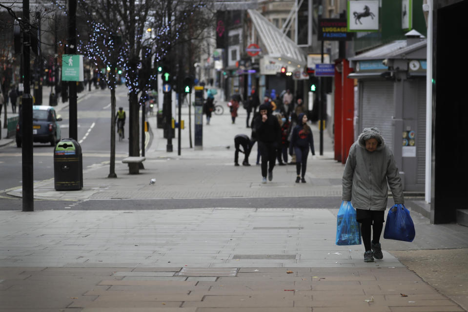 A view along Oxford Street in London, Saturday, Dec. 26, 2020. London is currently in Tier 4 with all non essential retail closed and people have been asked to stay at home, on what is usually one of the busiest retail days of the year with the traditional Boxing Day sales in shops. (AP Photo/Kirsty Wigglesworth)