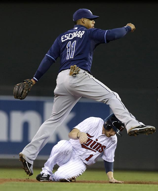 Tampa Bay Rays shortstop Yunel Escobar, left, leaps to clear Minnesota Twins' Alex Presley after the force at second to complete a double play in the first inning of a baseball game, Friday, Sept. 13, 2013, in Minneapolis. (AP Photo/Jim Mone)