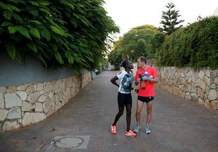 Lonah Chemtai, a Kenyan-born runner who will represent Israel in the women's marathon at the 2016 Rio Olympics, and her husband and coach, Israeli Dan Salpeter, speak before training near their house in Moshav Yanuv, central Israel July 14, 2016. REUTERS/Baz Ratner