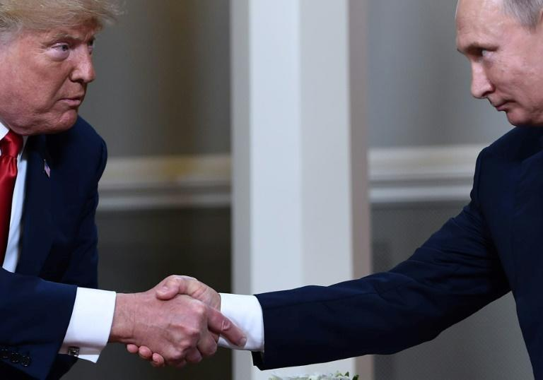 US President Donald Trump and Russian President Vladimir Putin shake hands ahead of a July 2018 summit in Helsinki that prompted criticism after Trump seemed to accept Moscow's denials of election meddling
