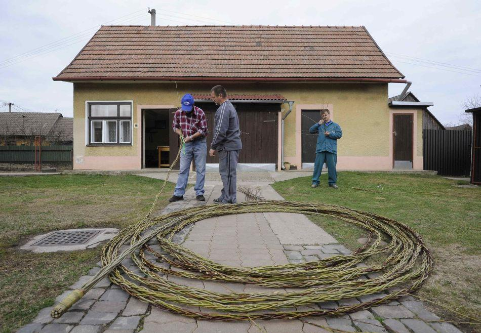 Brothers Ferdinand Kovac (C), Jaroslav Kovac (L) and Vladimir Kovac work on the longest Easter stick made from willow trees in their garden in the village of Horovce, 165 km (102 miles) north of Bratislava April 2, 2012. The 66 metre-long stick-willow will be the largest to be made in Slovakia and will qualify for entry in to the Slovakian Book of Records upon finishing. During Easter tradition Slovak boys symbolically whip girls on their legs in a custom believed to ensure a woman's fertility and beauty.