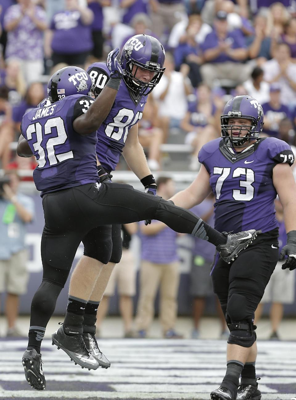 TCU running back Waymon James (32) is congratulated by teammate Buck Jones (80) after scoring a touchdown as Eric Tausch (73) looks on during the first half of an NCAA college football game against SMU Saturday, Sept. 28, 2013, in Fort Worth, Texas. (AP Photo/Brandon Wade)