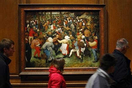 "People walks past a painting titled ""The Wedding Dance"" by artist Pieter Bruegel the Elder displayed at the Detroit Institute of Arts in Detroit"