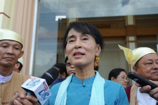 Myanmar opposition leader Aung San Suu Kyi talks to the media as she leave the lower house of parliament in July