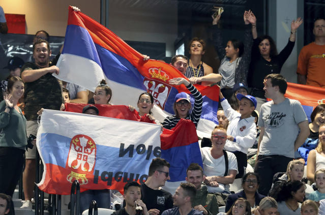 Supporters of Serbia's Novak Djokovic cheer him on during his first round match against Germany's Jan-Lennard Struff at the Australian Open tennis championship in Melbourne, Australia, Monday, Jan. 20, 2020. (AP Photo/Lee Jin-man)