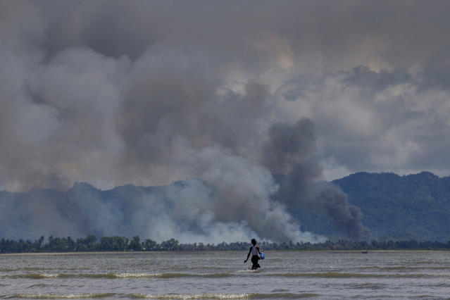 <p>A Bangladeshi boy walks towards a parked boat as smoke rises from across the border in Myanmar, at Shah Porir Dwip, Bangladesh, Thursday, Sept. 14, 2017. (Photo: Dar Yasin/AP) </p>