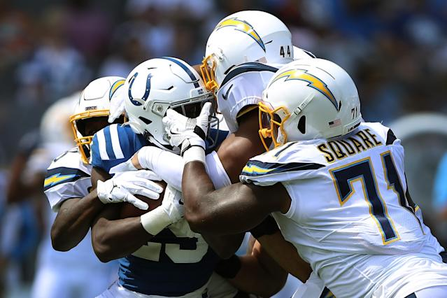 Marlon Mack #25 of the Indianapolis Colts is tackled by Kyzir White #44, Thomas Davis #58, and Justin Jones #93 of the Los Angeles Chargers during the first half of a game at Dignity Health Sports Park on September 08, 2019 in Carson, California. (Photo by Sean M. Haffey/Getty Images)
