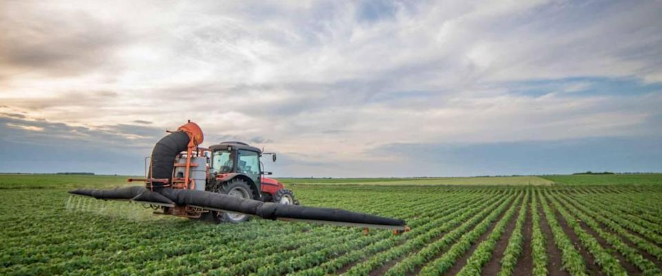 Tractor spraying pesticides in soybean fields