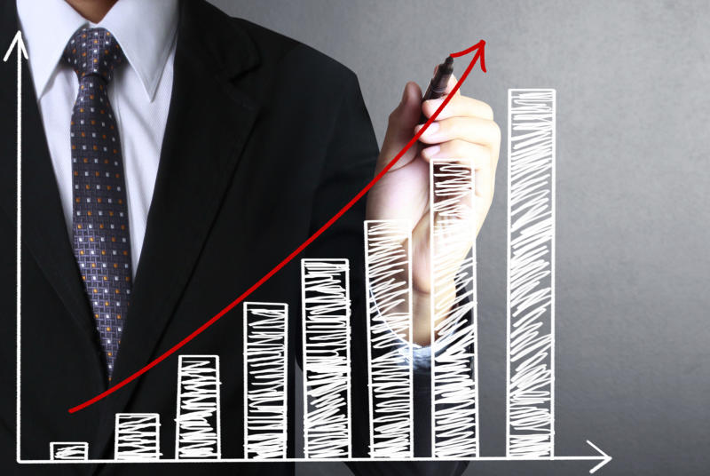 A man in a suit holding a pen stands in front of a drawing of an upward-sloping bar chart.