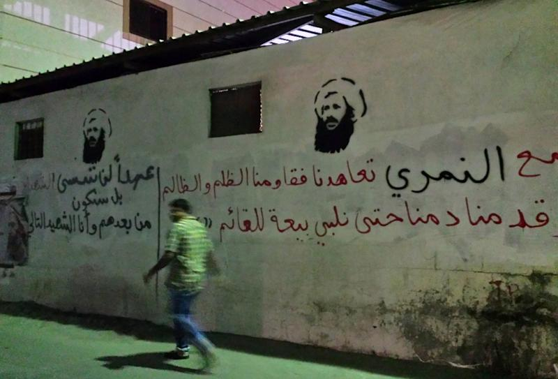 A man walks past images of executed Shiite cleric Nimr al-Nimr on a wall in the Awamiya area in Saudi Arabia's Eastern province, in a picture taken in 2016