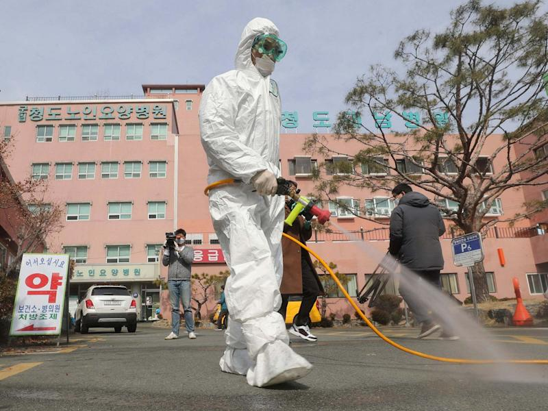 A worker wearing protective gears sprays disinfectant against the coronavirus in front of the Daenam Hospital in Cheongdo, where a 'special care zone' has been declared: Lim Hwa-young/Yonhap via AP