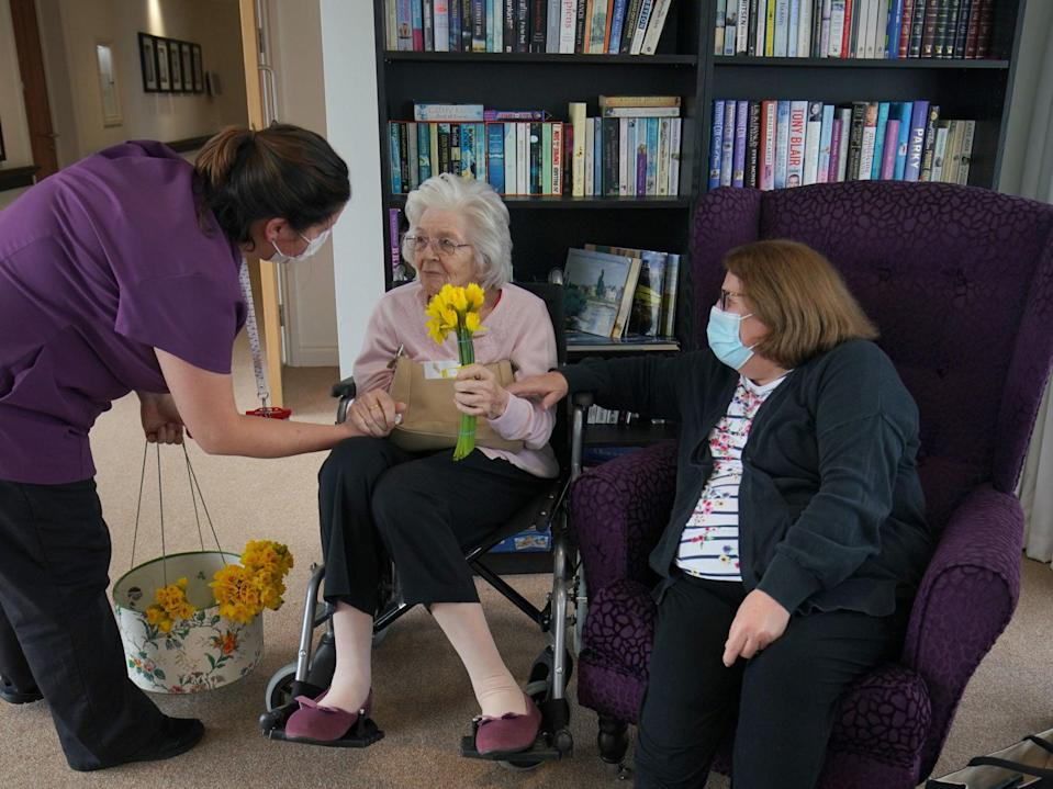 A member of staff gives a bunch of daffodils to Sylvia Newsom (centre) and her daughter Kay Fossett (right), who haven't seen each other since December, enjoy their first visit following the easing of rules at Gracewell of Sutton care home in South London (Aaron Chown/PA)
