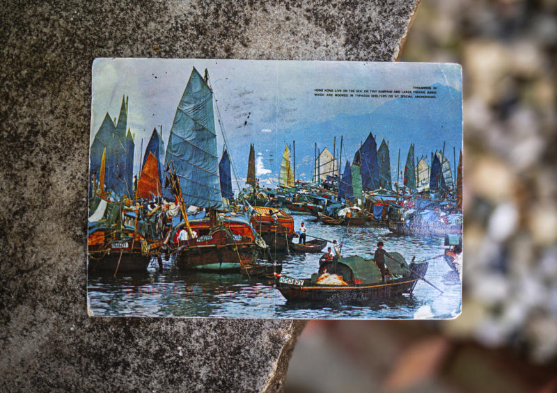 "Kim Draper received a postcard, which depicts a scene of fishing boats in Hong Kong, at her home in Springfield on July 8, 2019 that was postmarked and sent from Hong Kong exactly 26 years ago on July 8, 1993 to a previous family that lived at her address. Draper is trying to track down the family that the postcard was sent to, which was addressed to Leena and Muhammad Ali Kizilbash and is signed ""See you guys soon. Your Dad."" (Justin L. Fowler/The State Journal-Register via AP)"