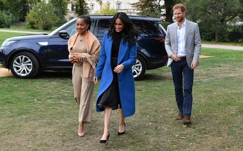 The Duke and Duchess with Meghan's mother, Doria (left) - Credit: BEN STANSALL/AFP