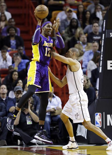 Los Angeles Lakers center Dwight Howard (12) passes past Miami Heat forward Shane Battier during the first half of an NBA basketball game, Sunday, Feb. 10, 2013, in Miami. (AP Photo/Wilfredo Lee)